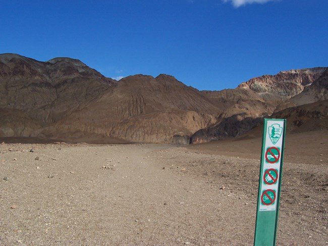A green wilderness barrier with symbols prohibiting motor vehicles and bicycles at the start of a canyon hike.