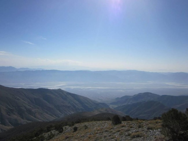 View into a valley with salt flats and mountain ranges