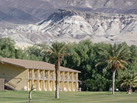 Hotel building with green grass lawn and palm trees in foreground.  Mountainous scenery in background.