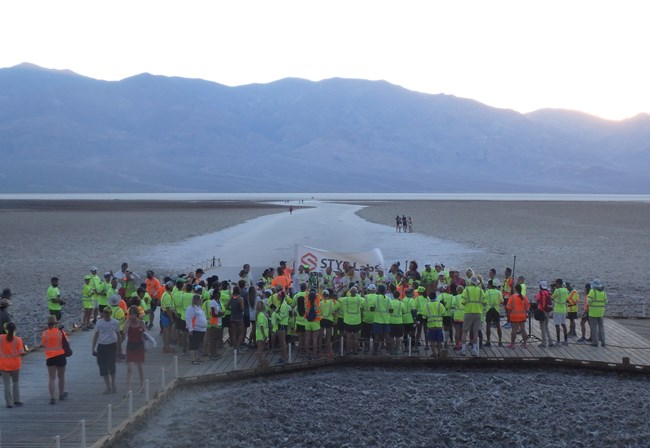 People in running gear stand waiting in a crowd on a vast salt flat.