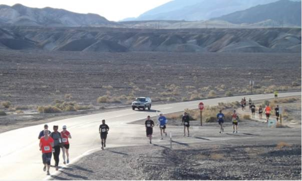 A group of runners along a paved road in a desert setting.