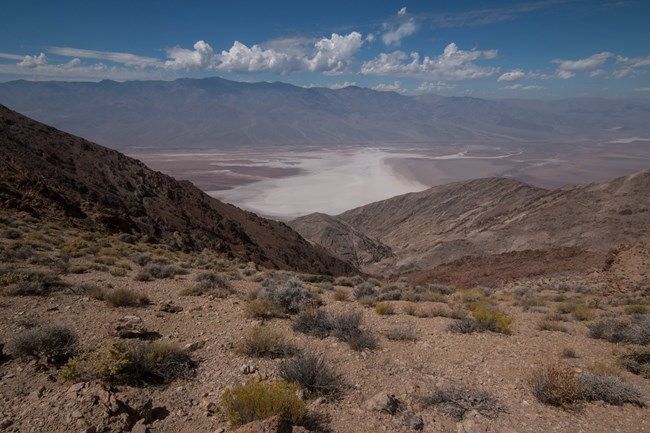 View from a rocky mountain ridge looking down on a vast salt flat.