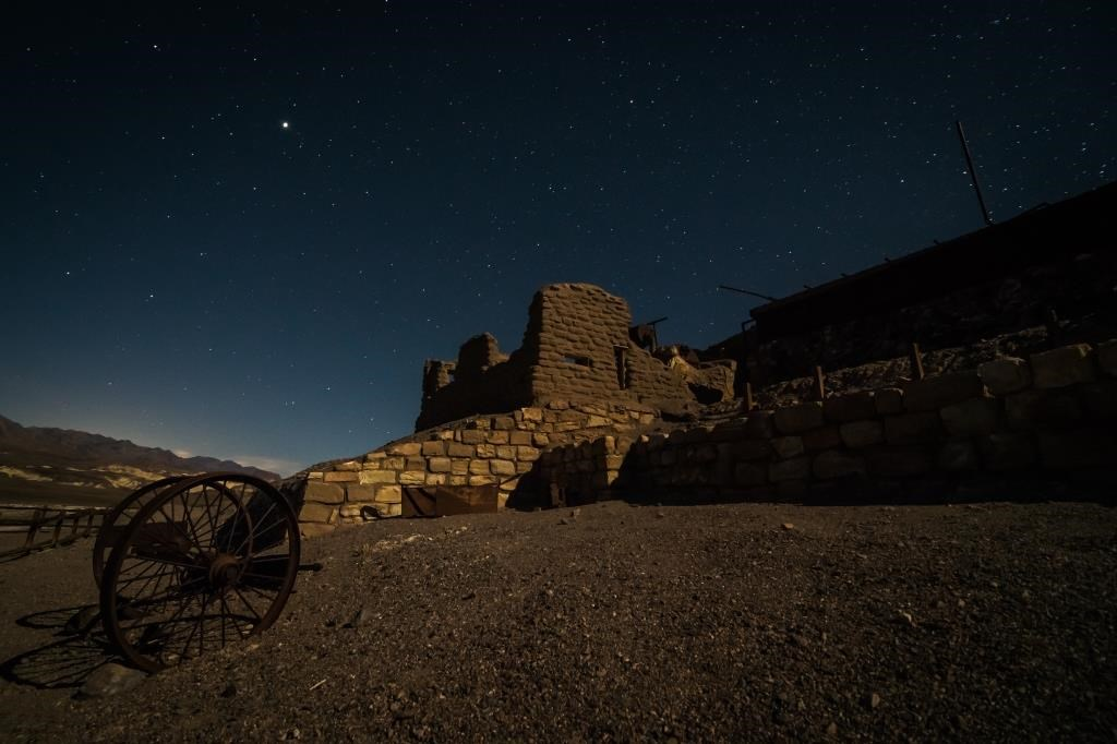 Mining ruins  of an adobe wall and a wagon wheel underneath a starlit sky