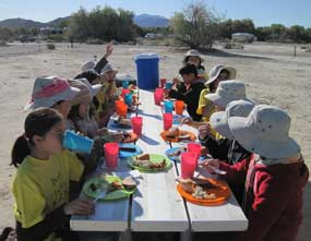 Students eat lunch on a picnic table.