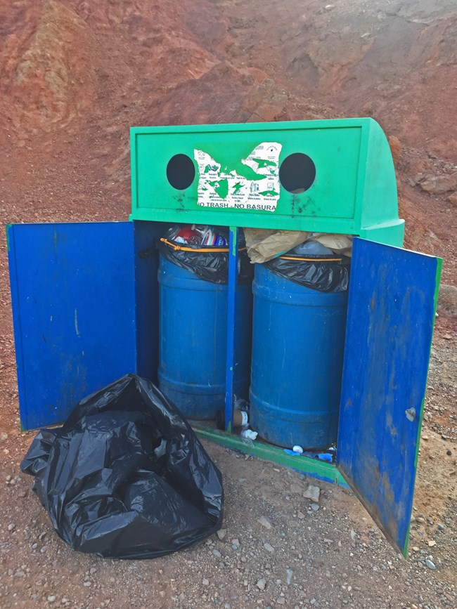 Two trash cans sit in an open box, with a full bag in front, in a desert landscape.