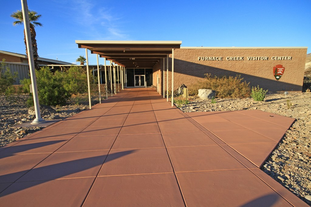 A sunlit walkway made of red concrete leads to Furnace Creek Visitor Center operated by the National Park Service
