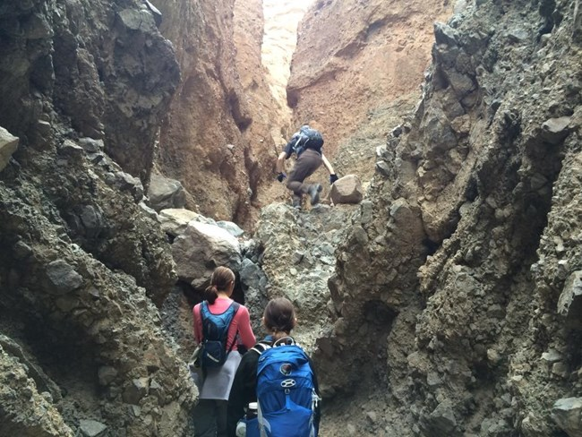 A hiker climbs a dryfall inside a narrow canyon while two other hikers prepare for their turns.
