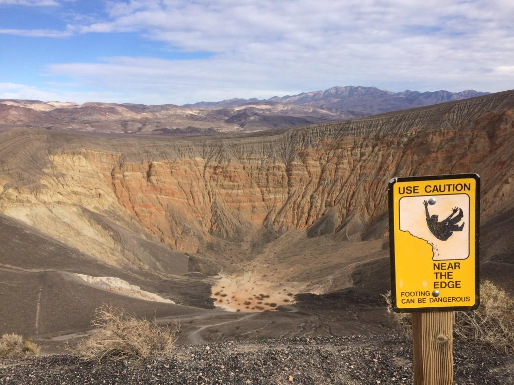 "A warning sign ""Use caution near edge"" with a graphic of someone falling is posted near the edge of a volcanic crater where hikers may travel a loop."