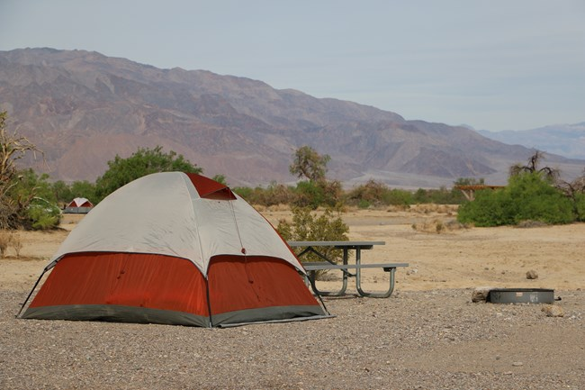 A tent sits in a flat, desert campground, next to a picnic table.