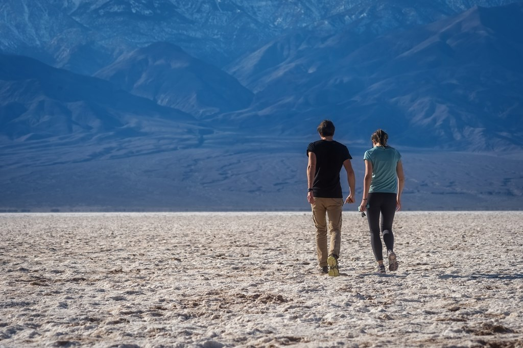 A man and woman walk out onto the white salt flats toward towering mountains in the distance.