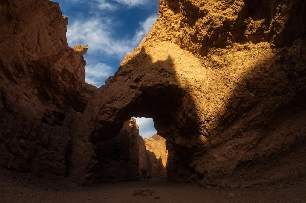 A natural bridge spans a desert canyon.