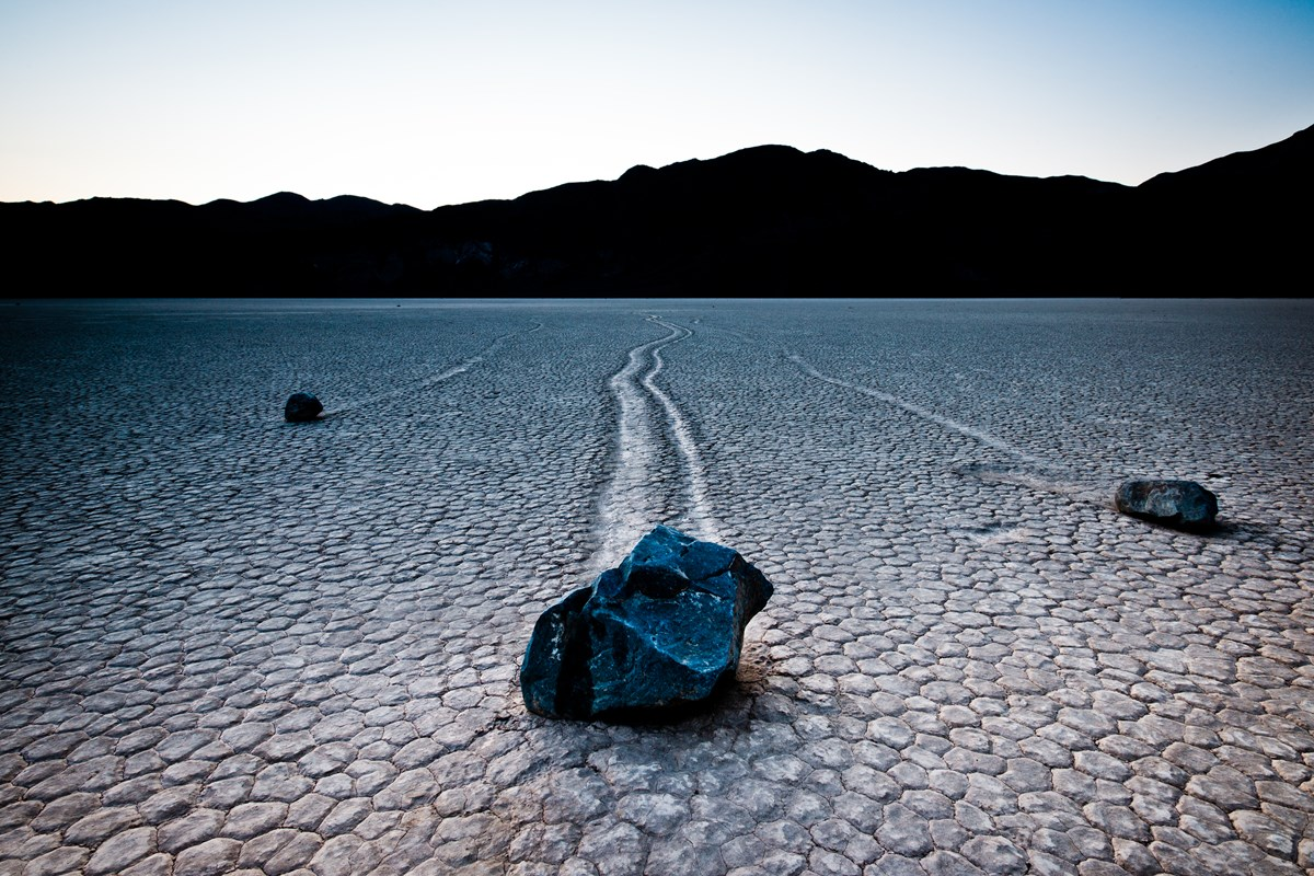 Boulders leave a mysterious trail in the surface of a dry lakebed.