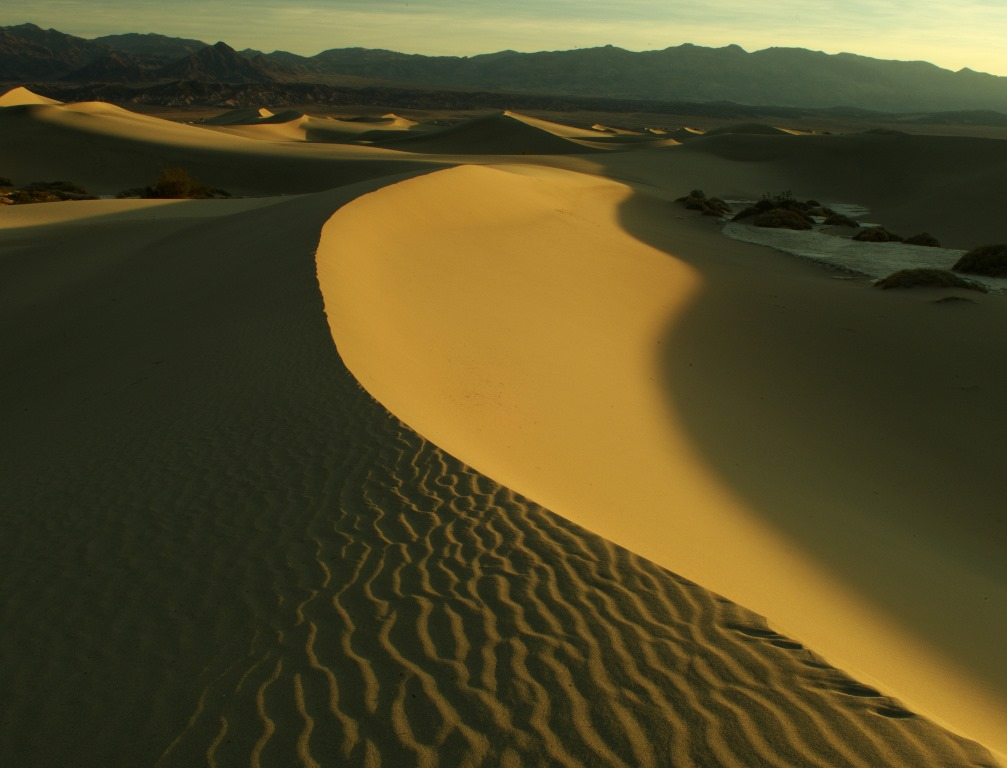 Sand dunes cover the valley while the sun illuminates only half of their rippled beauty as shadows accentuate in sharp contrast.