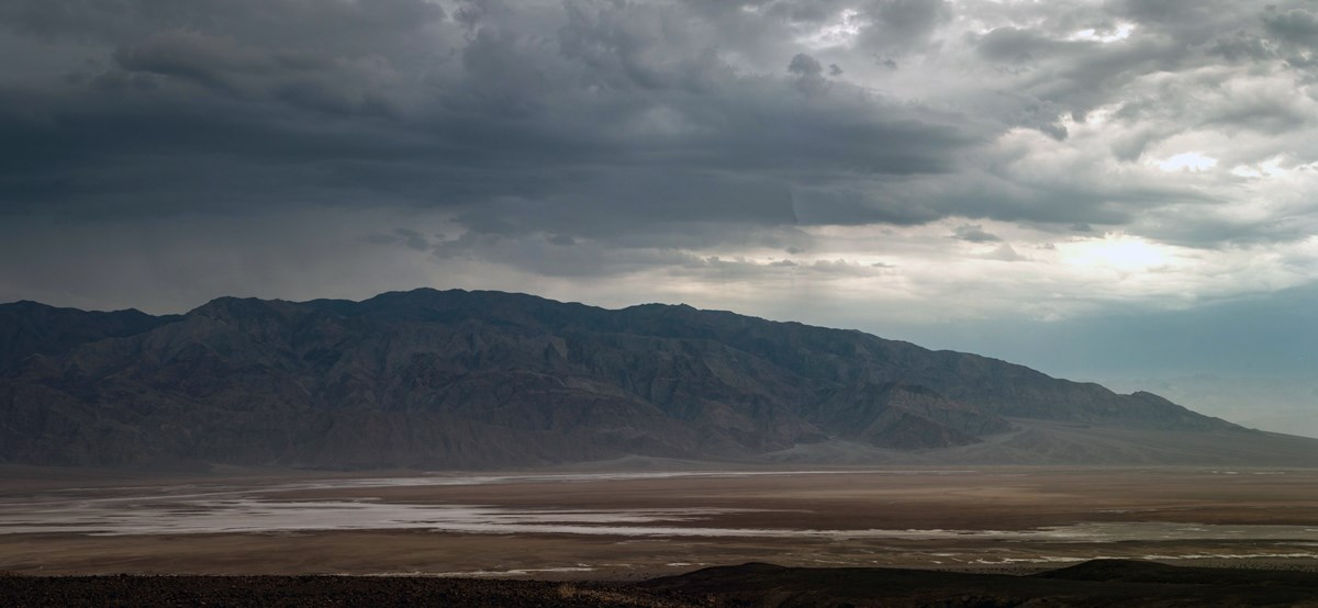 Distant desert mountains, in a cool light, sit under a large dark thunderstorm.