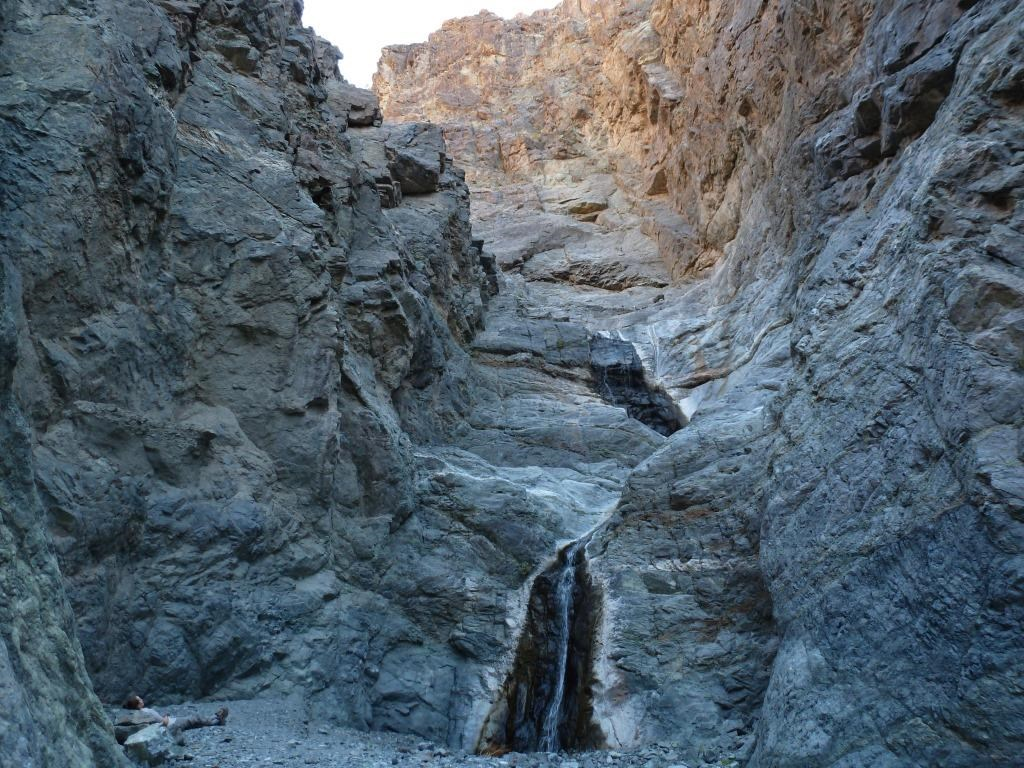 A two-tiered waterfall cascades over polished rock down a narrow canyon as a hiker rests on the ground to the left of the falls with her back against the canyon wall.