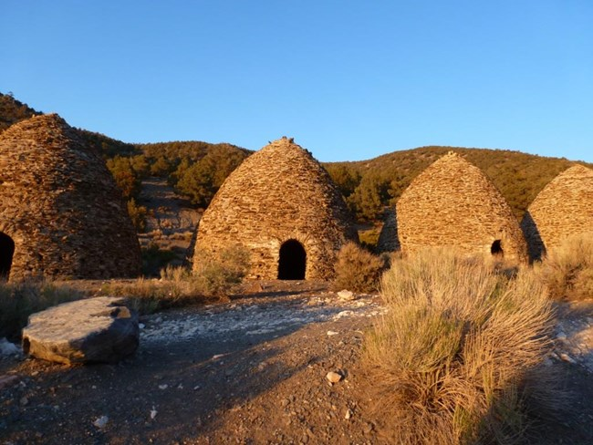Beehive shaped charcoal kilns made of rock line a forested mountain road.