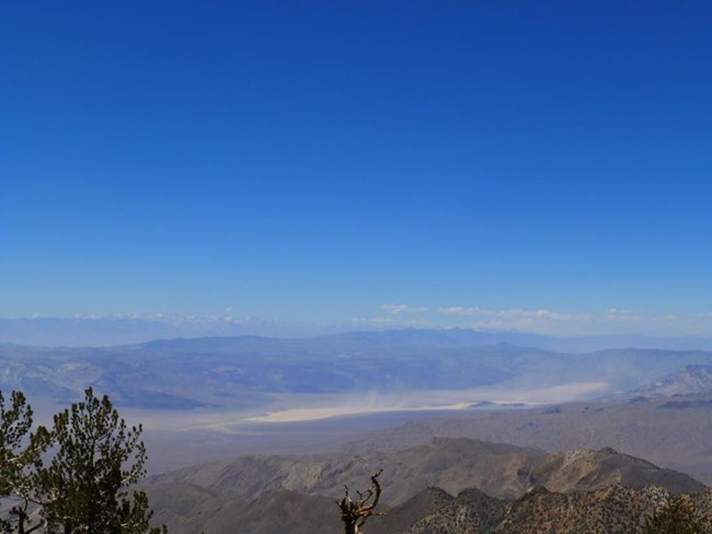 The view from the highest point in Death Valley to snow covered mountains on the horizon.