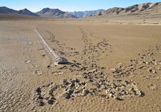 "Unfortunate footprints in the soft muddy surface of Racetrack playa surround one of the ""moving rocks""."
