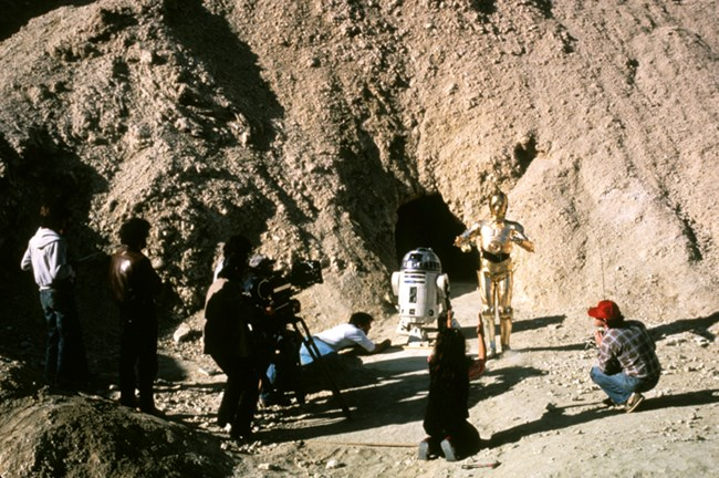 Two robots are surrounded by a few people filming them in a desert landscape.