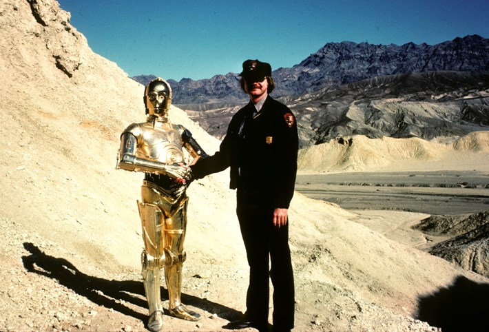 A gold robot shakes hands with a park ranger in the desert.