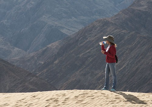 Aa woman drinks water while hiking on the dunes.