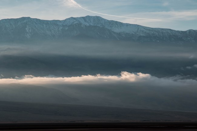 Fog lingers across desert mountains dusted with snow.