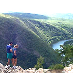 Hikers atop a mountain looking down at the river