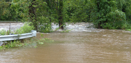 muddy creek overflowing its banks onto road