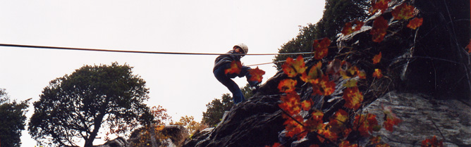 Climber on ropes descending a rocky cliff