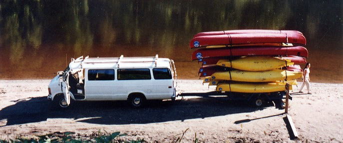 Van with canoes on a trailer on a river beach