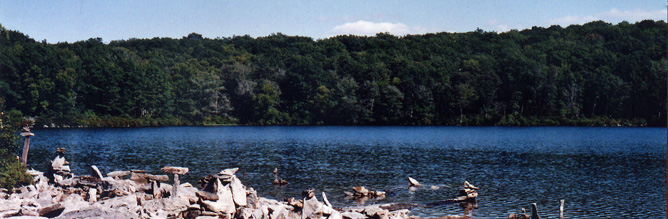 A large lake with forest on the far shoreline and rocks on the near shoreline