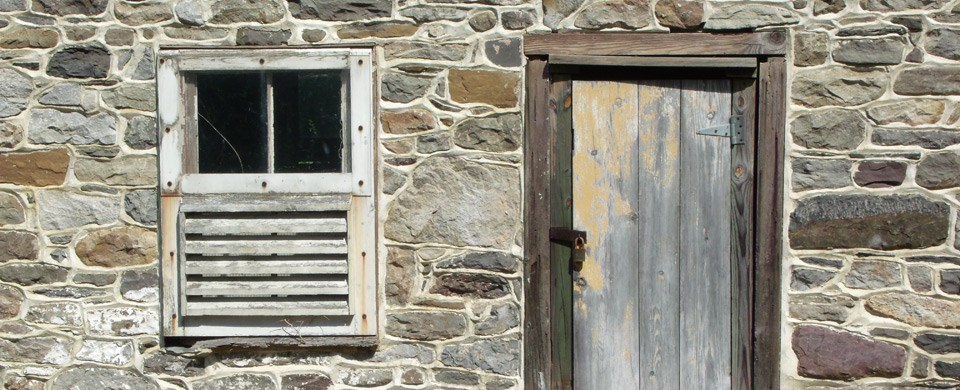 close up of old window and door on a stone building