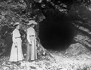 historic image of two ladies standing in front of a mine entrance