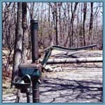 A metal water pump in a wooded area