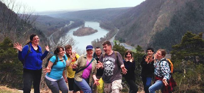 group of hikers in a silly pose on an overlook with the river in the background