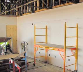 A work scaffold/ladder sits in front of a wall with newly installed drywall.