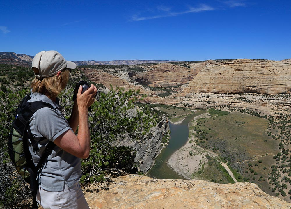 Woman with camera looking into canyon with river below