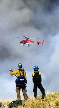 fire fighters with a helicopter above the horizon