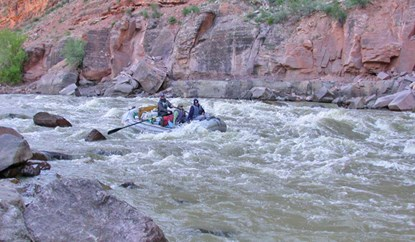 A raft with three people floats through the whitewater of Warm Springs Rapid.