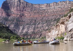 Several rafts float on the river and a canyon wall looms behind them.