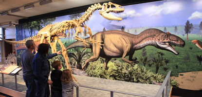 A family takes a look at an allosaurus replica and mural in the Quarry Exhibit Hall