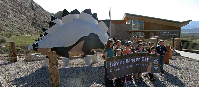 Vernal Cub Scouts hold the Junior Ranger Day Banner in front of the Quarry Visitor Center.