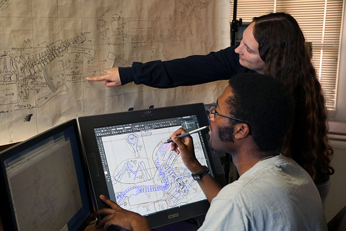 Using digitizing monitors and GIS software interns Nicole and Ben are converting and merging old quarry paper maps into a single electronic master map of one of the world's greatest dinosaur quarries.