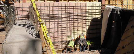 Three men work on rebar installation at the base of a wall.