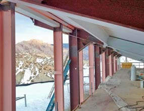 View of structural steel columns near the roof of the building and rugged, snowy landscape beyond.