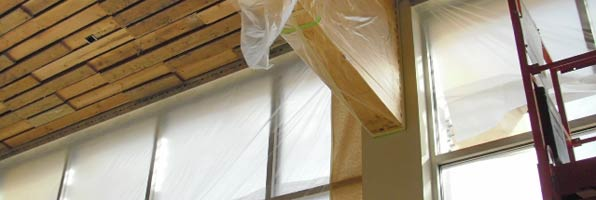 Wood on ceiling beam covered with plastic in preparation for painting walls of visitor center.
