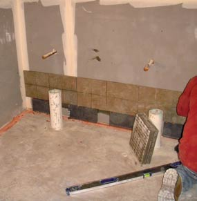 Installing tiles along the bottom of a wall in one of the bathrooms.