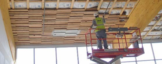 Man standing in a man lift installs wood on a partially completed tongue-and-groove ceiling.