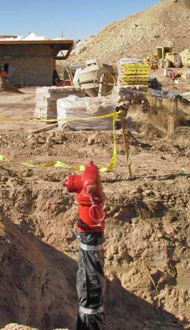 A new red fire hydrant is attached to pipe protruding from a large hole in the ground.