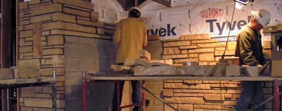 Two stone masons work on the stone veneer inside the Quarry Visitor Center.